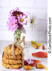 A stack of cookies tied with a rope next to autumn leaves and a vase of flowers on the table.