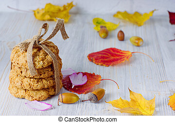A stack of cookies tied with a rope next to autumn leaves on the table. Autumn still life.