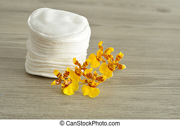 A stack of cotton pads with yellow orchids