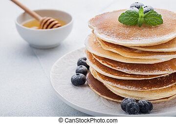 A stack of delicious pancakes with honey and blueberries on a light blue background
