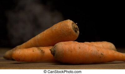 A stack of fresh carrots from the refrigerator that blows...