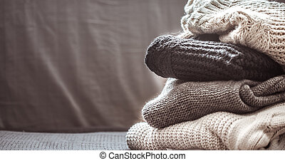 A stack of knitted sweaters ,the concept of warmth and...