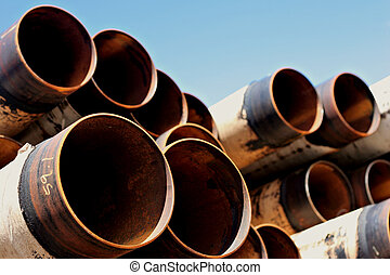 a stack of large, rusting steel pipes, against a blue sky