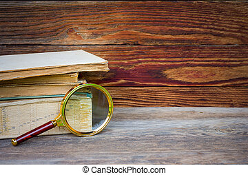 a stack of old books and magnifier on wooden background with space for text