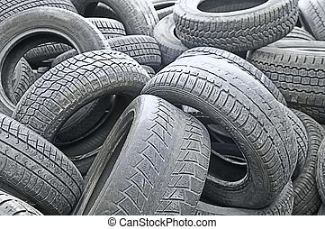 a stack of old run-down tires on a auto repair shop