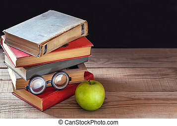 A stack of old vintage books and one green apple on a rustic wooden table.