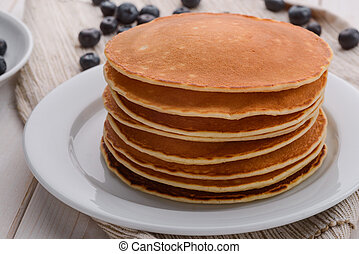 A stack of pancakes on the white plate. Berries are scattered over the table. A nourishing meal. Breakfast in American style.