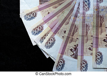 A stack of Russian banknotes of five hundred rubles on a dark background close up