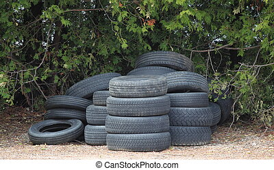 A stack of tires - A stack of used old tires sit in a yard...