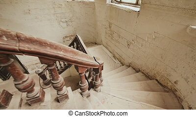 A staircase with a dark wooden railings in an abandoned architectural building. The legacy of the past. Shooting in motion with electronic stabilization.