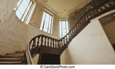 A staircase with wooden railing in an abandoned architectural building. The legacy of past architectural times. Handrail stairs made of dark wood.
