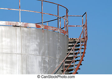 stairway casts a heavy on an old silver storage tank. Stairs
