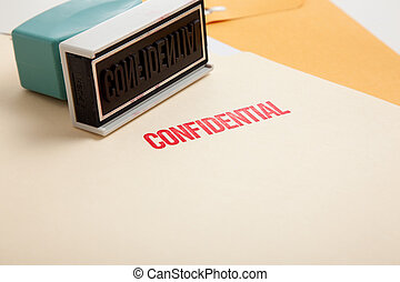 """A stamp with the word \""""confidential\"""" on a stack of folders"""