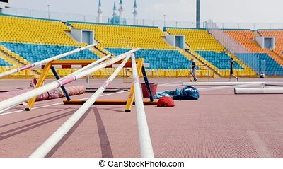 A stand in the stadium for the pole vault poles - people...