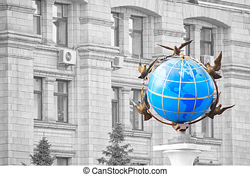 A statue of a blue terrestrial globe with doves of peace...