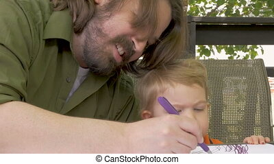A stay at home dad drawing with his baby boy as he watches...
