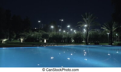 A steadicam shot of an illuminated open pool at night - A...
