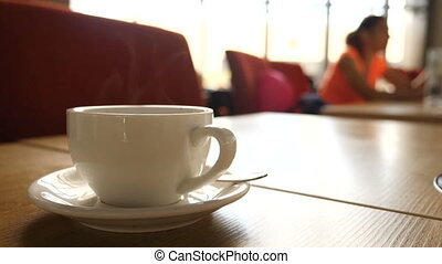 A steaming hot mug of coffee with blurred people moving in the background.