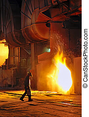 A steel worker in factory - A steel worker takes a sample...
