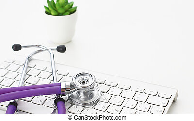 A stethoscope is on the keyboard of a computer