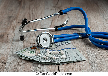 A stethoscope lies on a bundle of money and pills on a light wooden background. The concept of expensive medicine, medical insurance, expensive drugs. Copy space.