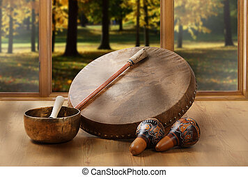 A still life of the shamanic drum, Tibetan singing bowls and...