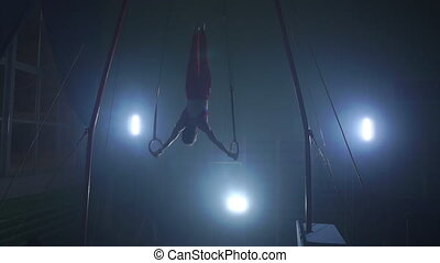 a Still shot of a guy working out on the still rings a...