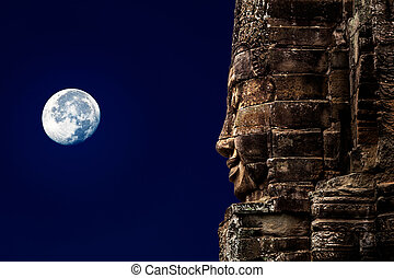 A stone sculpture of Buddha on the background of the night...