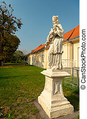A stone sculpture of Saint Johannes Nepomuk in Vienna, on a sunny day in summer