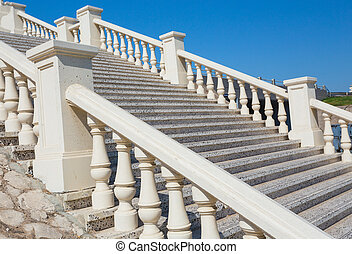A stone staircase with white balustrade
