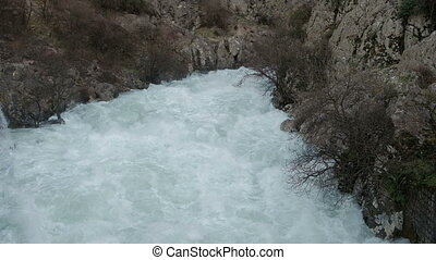 A stormy mountain river flows widely among the mountains. In...