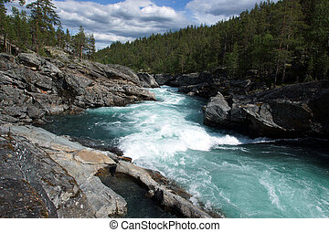 A stormy river stream with noise flows through the rocks and forest in Norway, clear transparent blue water