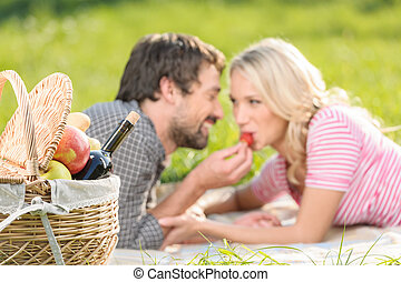 A strawberry for her. Young men feeding his girlfriend with strawberry lying on the grass in spring park