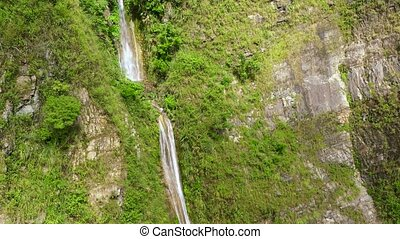 A stream of water from a cliff in the jungle. Cascade Waterfall on Luzon Island, Philippines.