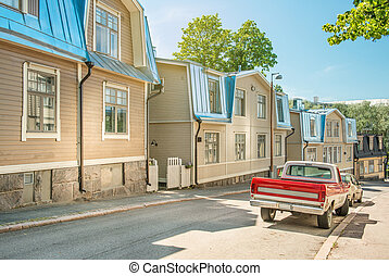 A street in Helsinki on a sunny summer day. Traditional finnish wooden houses in a quiet cozy street, Finland