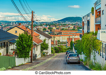 A street in Oslo, Norway. Beautiful view from a hill with old wooden houses to the city center with colorful architecture