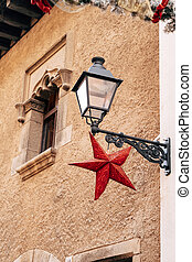 A street lamp on a bracket on the wall of a house with a red star at the window with patterns in stone.