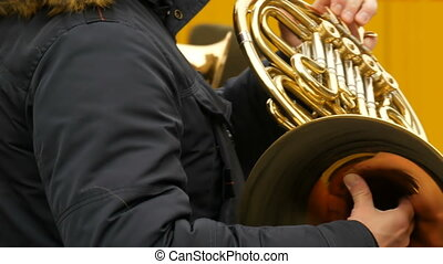 A street musician playing the French horn close up view. - A...