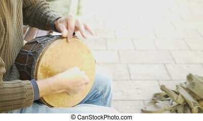 A street musician plays on an African drum. Man playing on a Bongo drum . close up. Hand tapping a Bongo drum . 4k, slow-motion shooting. sun glare