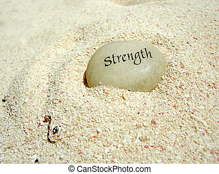 a strength stone in the sand on a beach