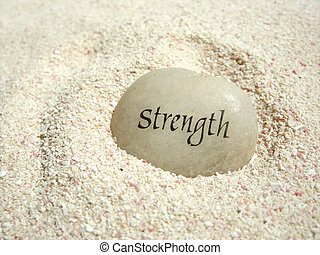 strength stone - a strength stone in the sand on a beach