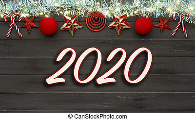 A string of christmas star decorations, lights and tinsel, with 2020 written in the middle, on destressed dark wood
