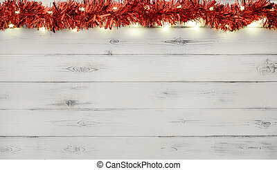 A string of red and silver christmas lights and tinsel, on destressed white wood