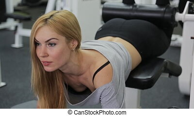 A strong athlete, blonde women with muscular body doing exercise on the buttocks and legs straining their muscles in the gym.