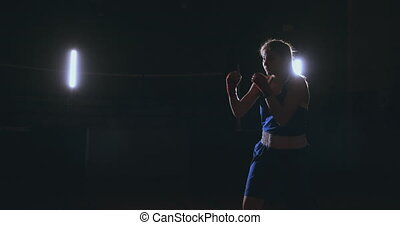 A strong athletic, woman boxer, boxing at training on the black background. Sport boxing Concept with copy space.