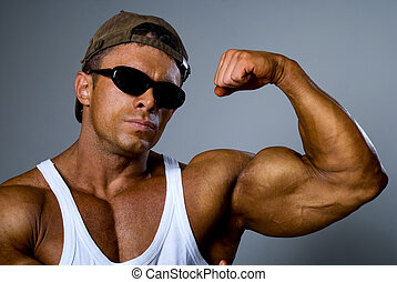 A strong man in sunglasses shows his muscles. Trained body. ...