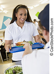 A student collecting lunch from the school cafeteria
