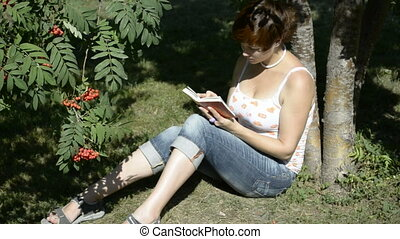 A student reads a book in the park
