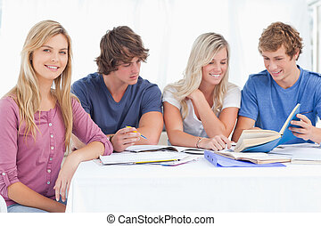 A study group working hard as one girl smiles and looks at the camera