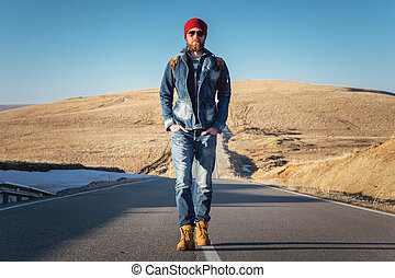 A stylish bearded hipster in sunglasses with a vintage backpack walks along the asphalt road on a sunny day. The concept of hitchhiking and hiking